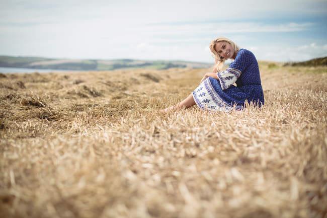 Nivel de superficie de la hermosa mujer rubia sentada en el campo - foto de stock