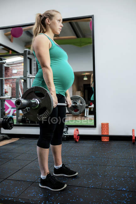 Pregnant woman working out with barbell at gym — Stock Photo