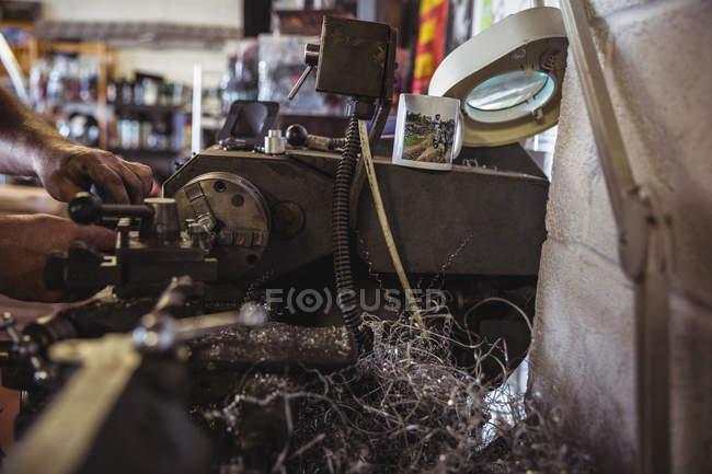 Mechanic working on industrial lathe machine in workshop — Stock Photo