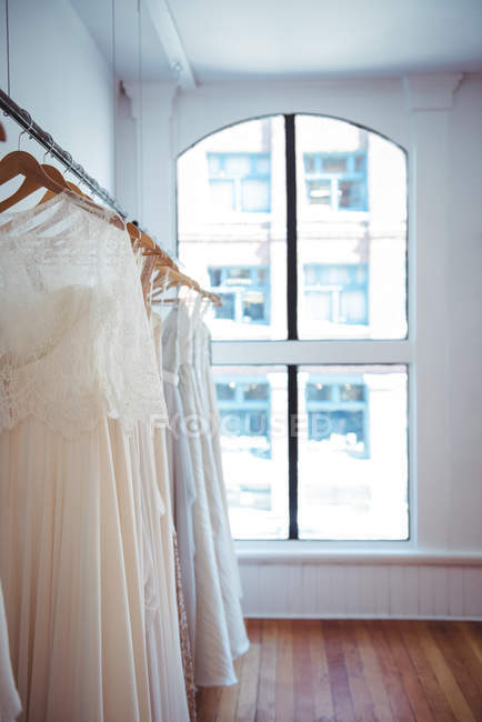 Various wedding dress hanging on clothes line in a shop in studio — Stock Photo