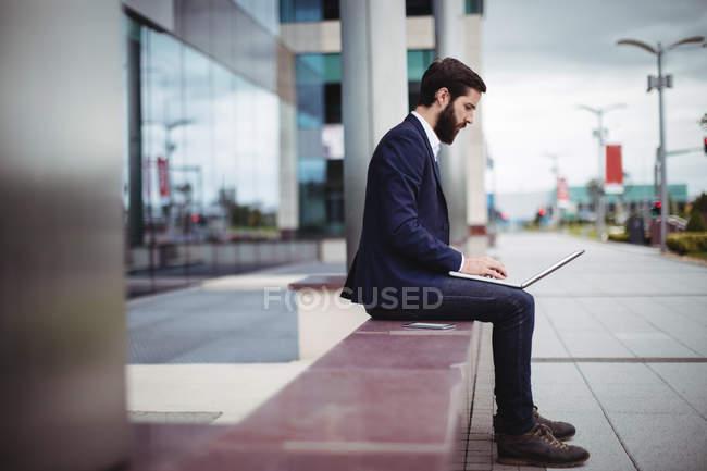 Empresário sentado na passagem do prédio de escritórios e usando laptop — Fotografia de Stock
