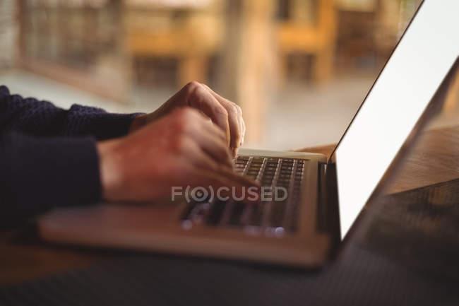 Primer plano del hombre con laptop en barra de bar - foto de stock