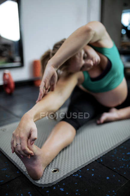Selective focus of Pregnant woman performing stretching exercise on exercise mat in gym — Stock Photo