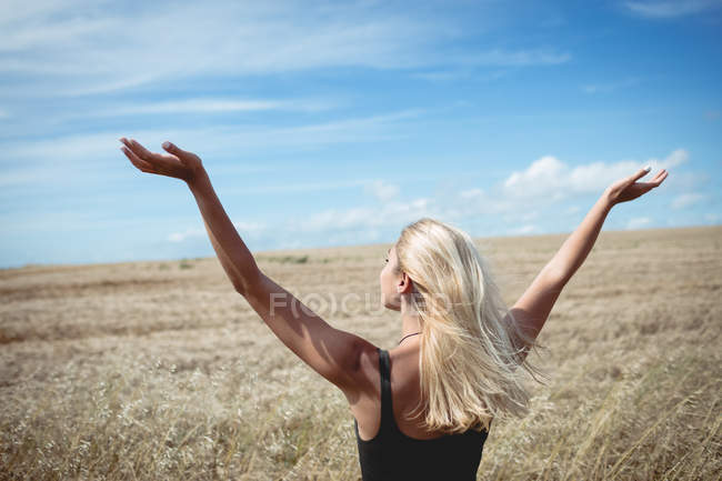 Back view of blonde woman standing in field with open arms — Stock Photo