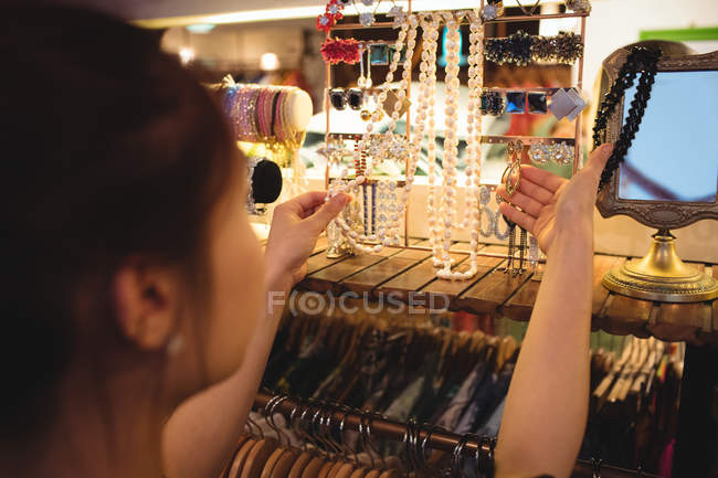 Stylish woman selecting jewellery in a antique jewellery shop — Stock Photo