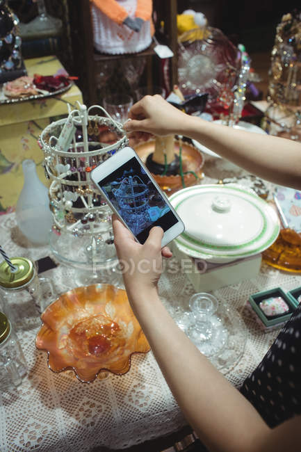 Female hands photographing jewelry in antique jeweler shop — Stock Photo