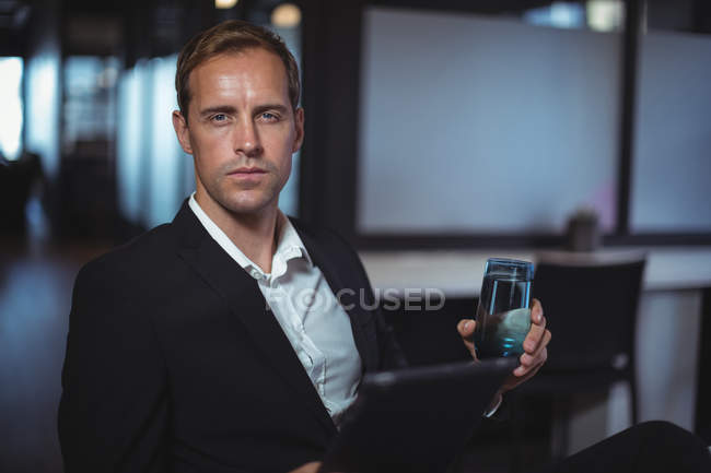 Portrait of businessman sitting in office with a glass of water and digital tablet — Stock Photo