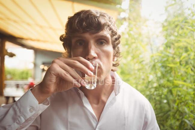 Portrait of man having tequila shot in bar — Stock Photo