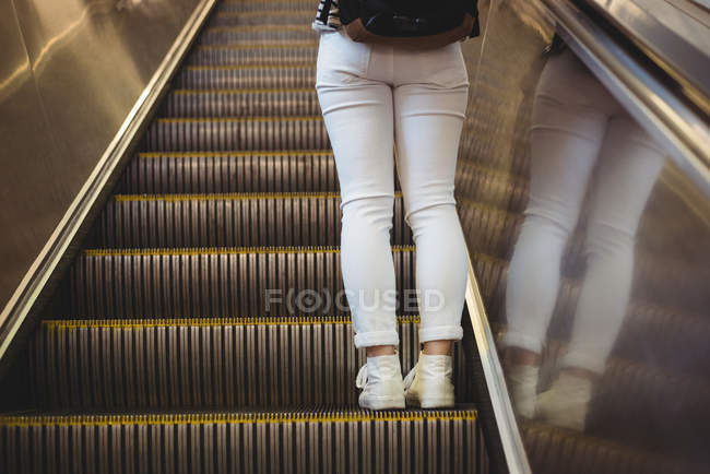 Low section of woman standing on escalator — Stock Photo