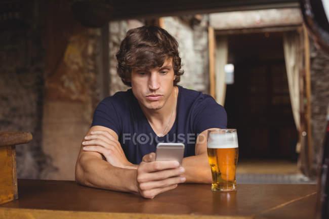 Человек, использующий мобильный телефон со стаканом пива на столе в баре — стоковое фото