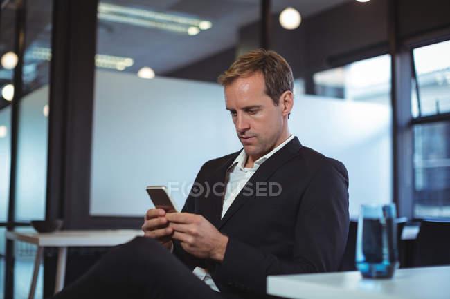 Homme d'affaires à l'aide de téléphone portable au bureau — Photo de stock