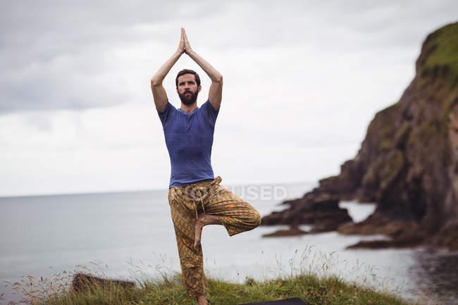 Человек, занимающийся йогой на скале — стоковое фото