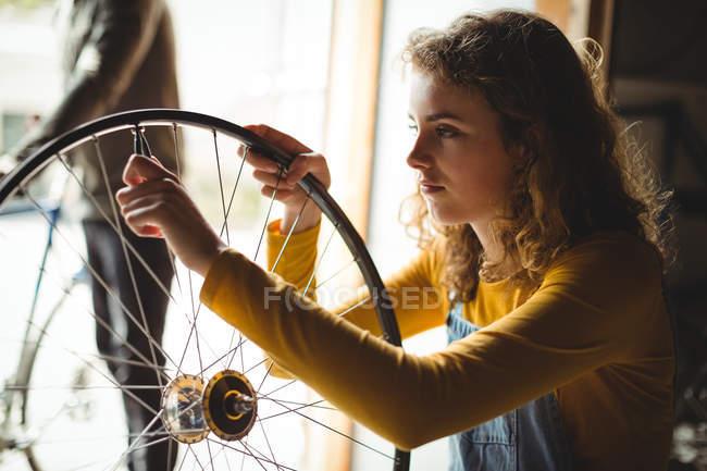 Examinar una rueda de bicicleta en taller mecánico - foto de stock