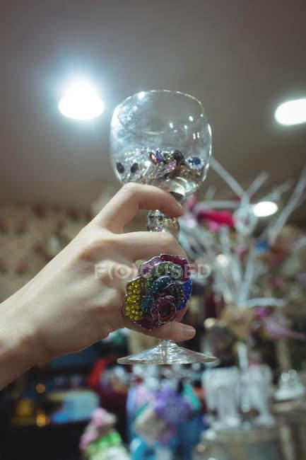 Weibliche Hand hält Tasse mit Schmuck in antiken Juwelier — Stockfoto