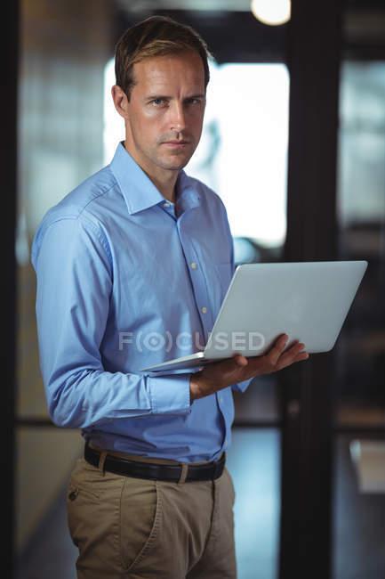 Portrait d'un homme d'affaires réfléchie utilisant l'ordinateur portable au bureau — Photo de stock