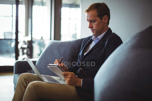 Businessman sitting on the sofa with laptop and writing notes in diary at office — Stock Photo