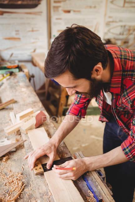 Людина, що працює над дерев'яна Планка на верфі — стокове фото