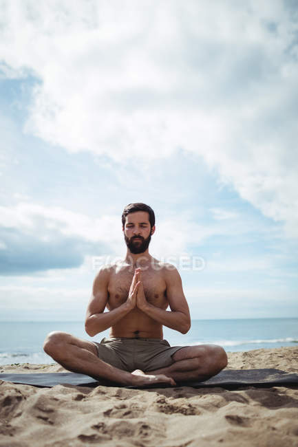 Homme effectuant du yoga sur la plage — Photo de stock