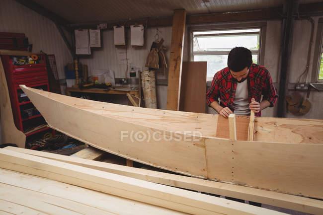 Человек готовит деревянный каркас лодки на верфи — стоковое фото