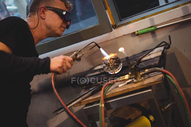 Ventilateur donnant la touche finale à un morceau de verre avec torche soufflante à l'usine de soufflage du verre — Photo de stock
