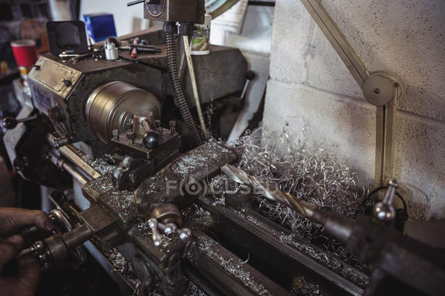 Mechanic working on industrial lathe machine in workshop — Stock Photo