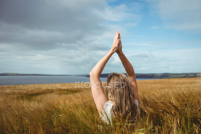 Back view of Woman with hands raised over head in prayer position in field on sunny day — Stock Photo