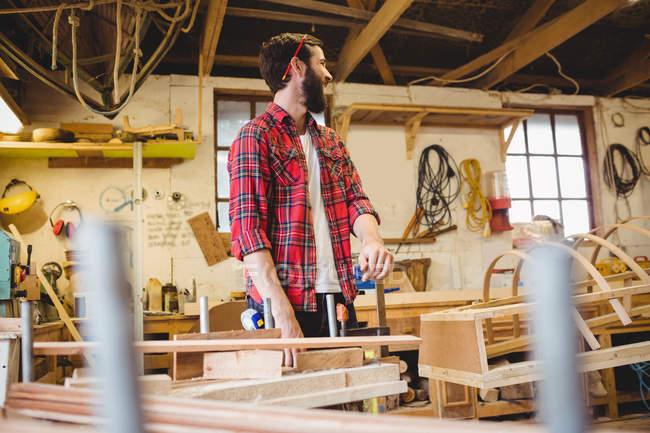 Человек, работающий над деревянной доской на верфи — стоковое фото