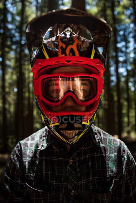 Портрет велосипедиста-мужчины в шлеме и очках, стоящих в лесу — стоковое фото