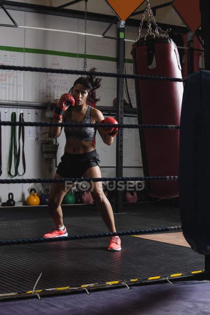 Boxerin übt Boxen mit Boxsack im Fitnessstudio — Stockfoto