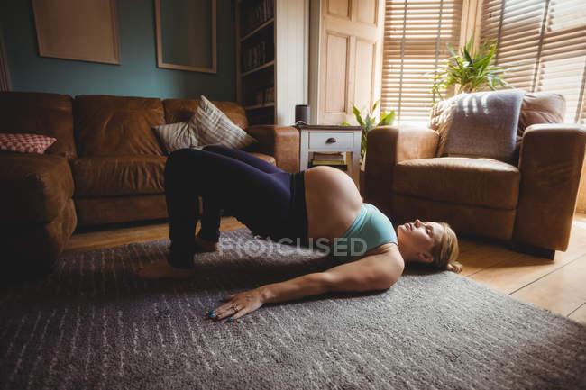 Vista laterale della donna incinta eseguendo stretching esercizio nel salotto a casa — Foto stock