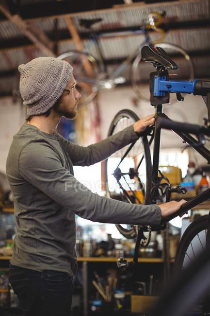Механік вивчення велосипеда в майстерню з ремонту велосипедів — стокове фото