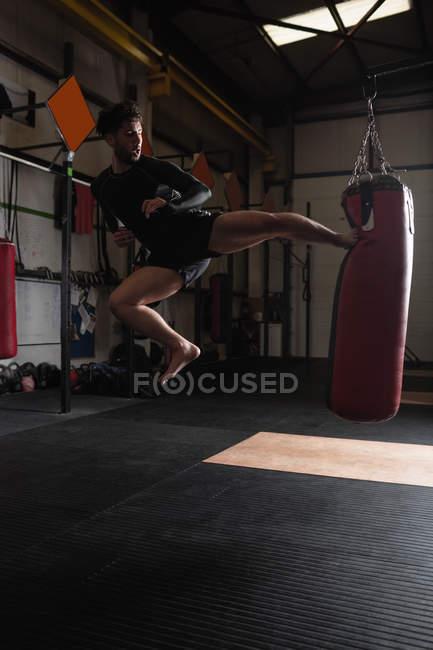 Sportlicher Boxer übt Boxen mit Boxsack im Fitnessstudio — Stockfoto