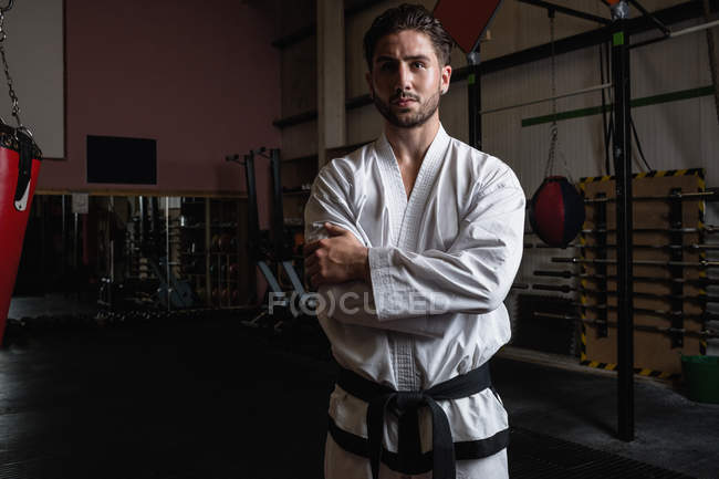 Portrait of handsome man in karategi standing with arms crossed in fitness studio — Stock Photo