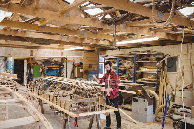 Man Preparing Wooden Boat Frame In Boatyard One Person Casual