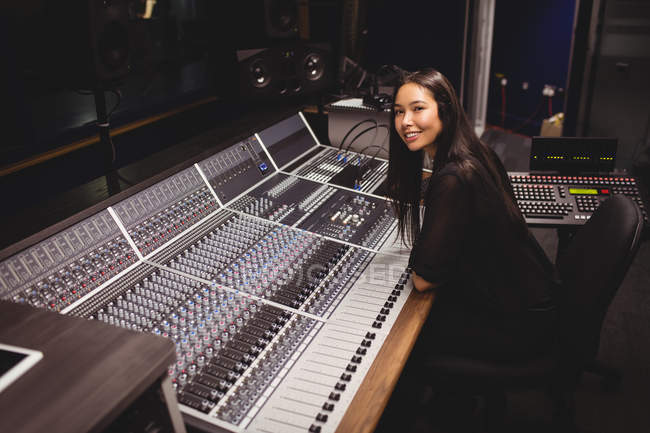 Female student using sound mixer in a studio — Stock Photo