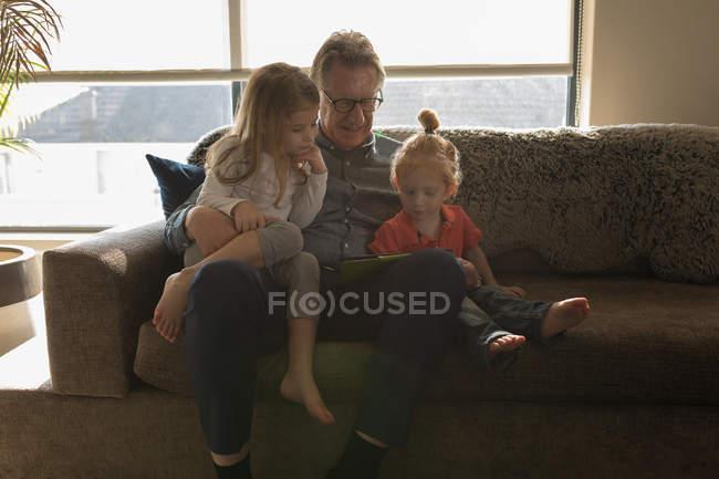 Großvater und Enkelin mit digitalem Tablet im heimischen Wohnzimmer — Stockfoto