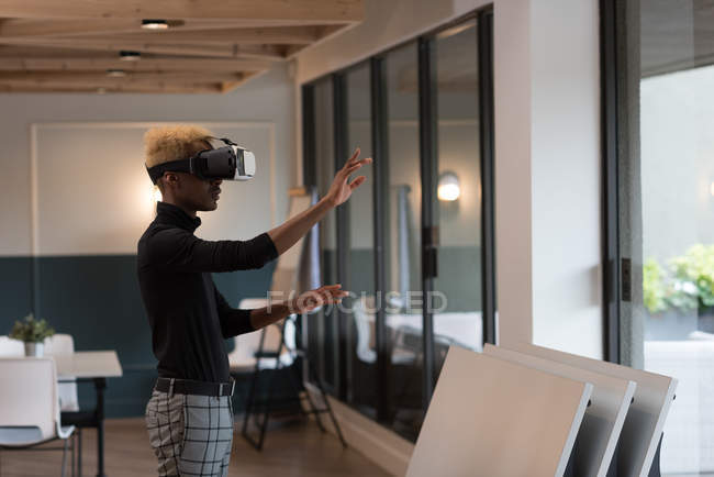 Side view of businessman using virtual reality headset in office — Stock Photo