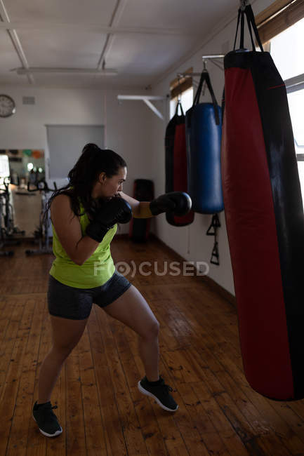 Young female boxer practicing boxing in fitness studio — Stock Photo