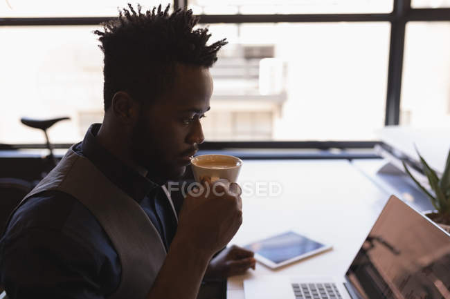 Smart businessman having coffee in office — Stock Photo