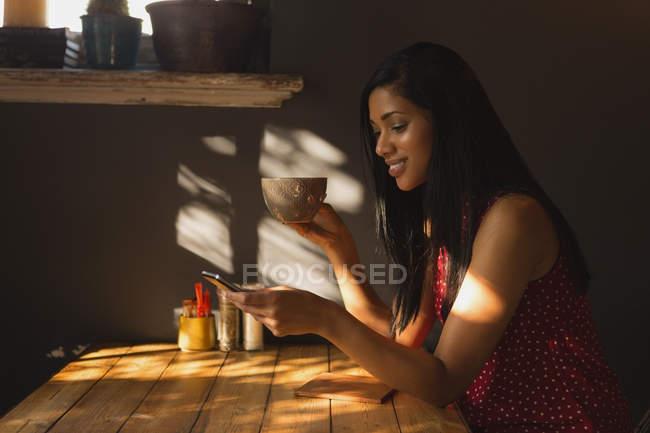 Вид сбоку женщины с помощью мобильного телефона имея кофе в кафе — стоковое фото