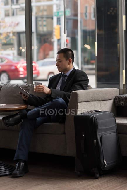 Бизнесмен, употребляющий виски при использовании цифрового планшета на диване в отеле — стоковое фото