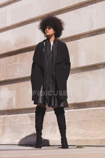 Продуманий жінку, що стояли в місті сонячний день — стокове фото
