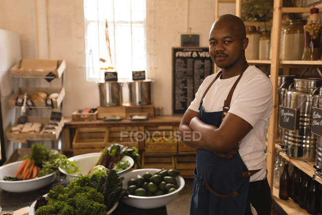 Portrait of male staff standing with arms crossed in supermarket — Stock Photo