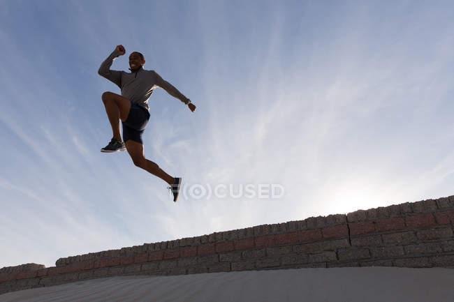 Низький кут зору чоловіча спортсмен, перестрибуючи з навколишніх стіни — стокове фото