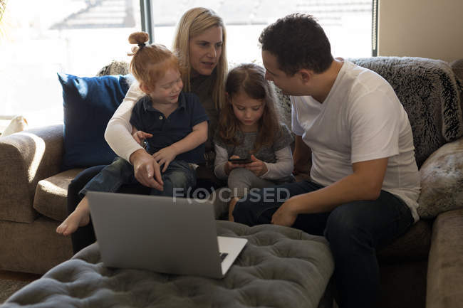 Сім'ї, які взаємодіють один з одним на дивані у вітальні на дому — стокове фото
