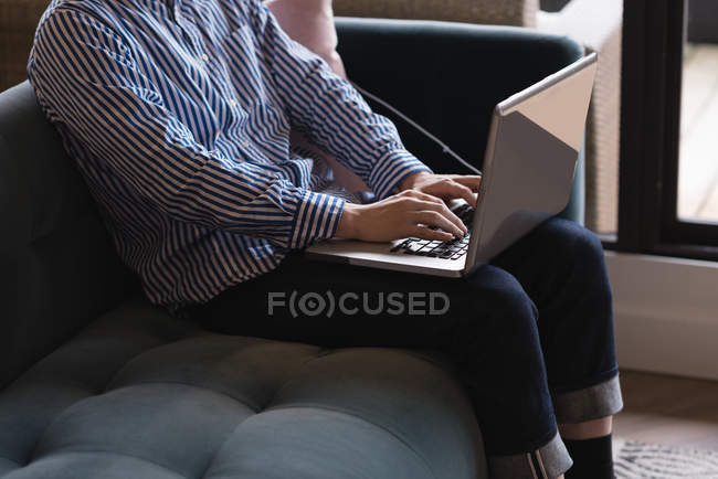 Mid section of male executive using laptop in office — Stock Photo