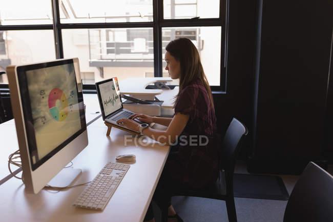 Бизнесмен, использующая ноутбук за столом в офисе — стоковое фото