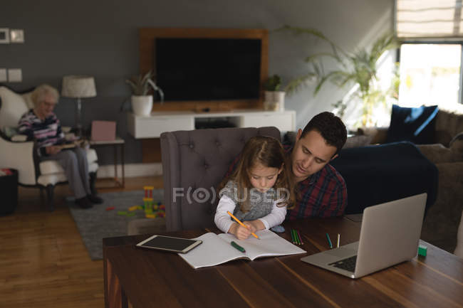 Father helping his daughter in studies in living room at home — Stock Photo