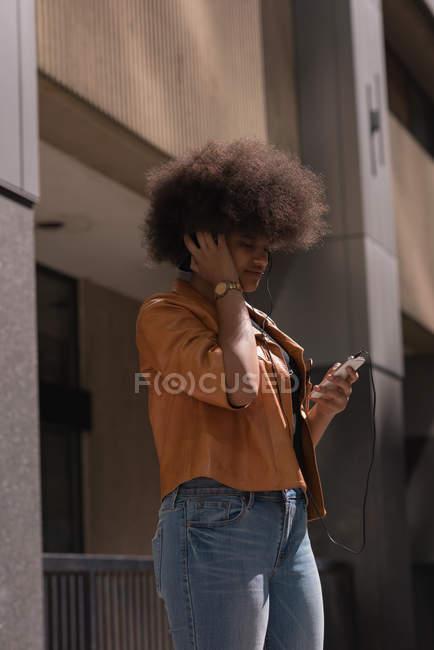 Женщина слушает музыку на мобильном телефоне в городе — стоковое фото