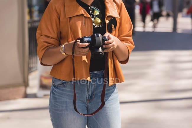 Mid section of woman reviewing photos on camera — Stock Photo